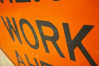 Part of an orange Road Work sign showing the word work