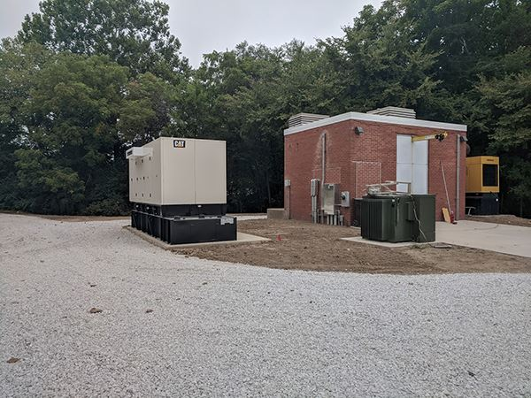 Large generator sitting outdoors next to a small brick building