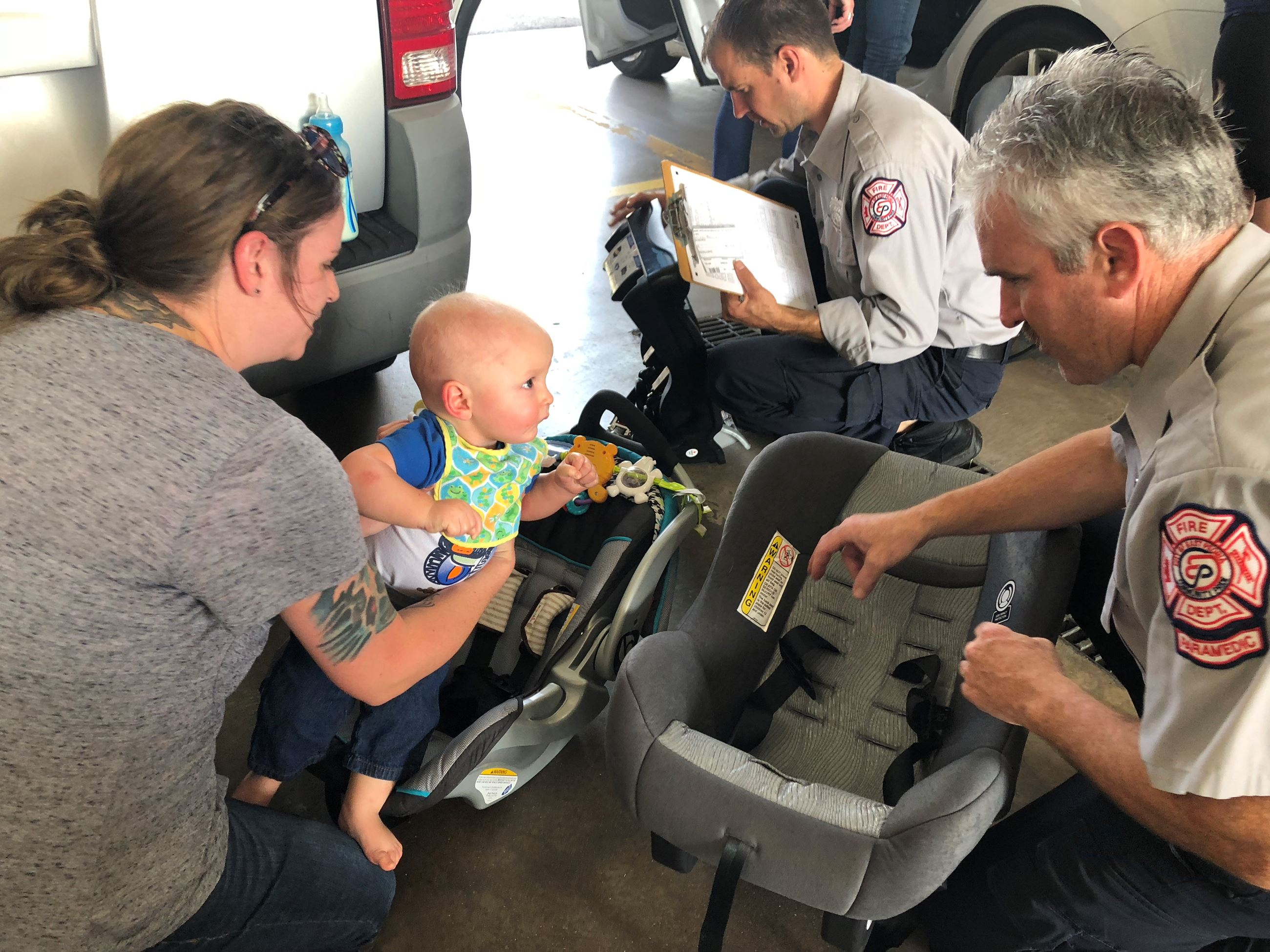 Mom and firefighters checking baby&#39s car seat