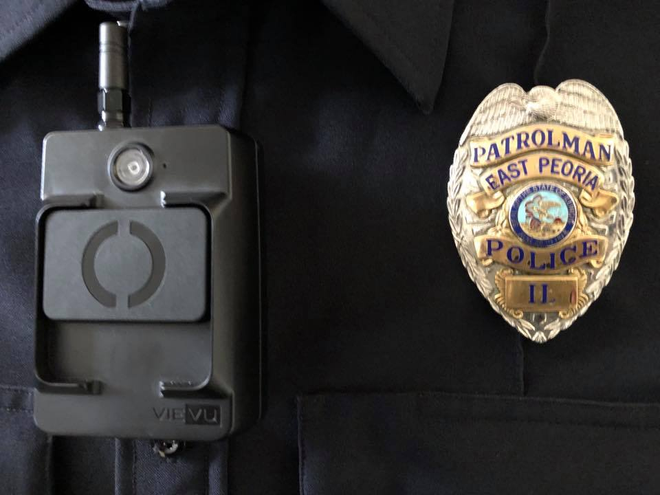 Picture of a police body camera and a police badge